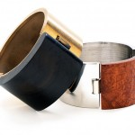 Stainless cuff bracelet; briar root and silver lined buckle bronze cuff bracelet; ebony and bronze lined buckle.